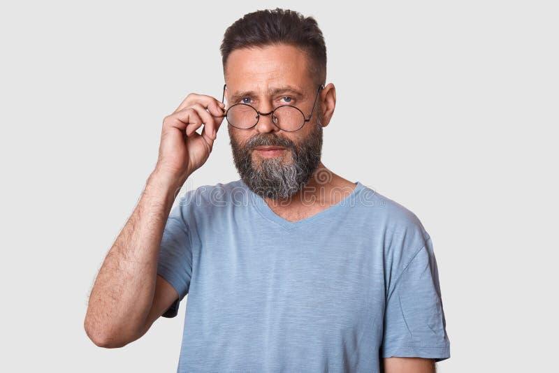 帅哥演播室射击被隔绝在白色背景,看直接地照相机,保留在他的眼镜的手,有时髦 免版税库存图片
