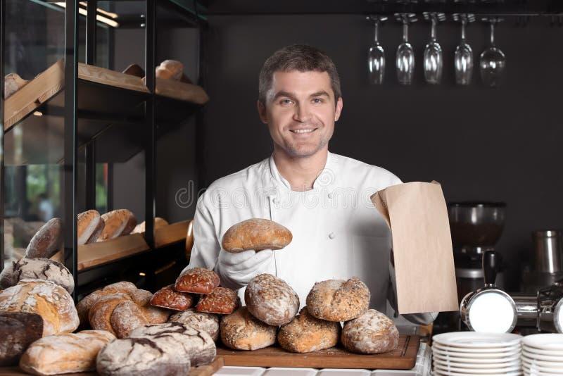 帅哥用运作在面包店商店的新近地被烘烤的面包 免版税库存照片