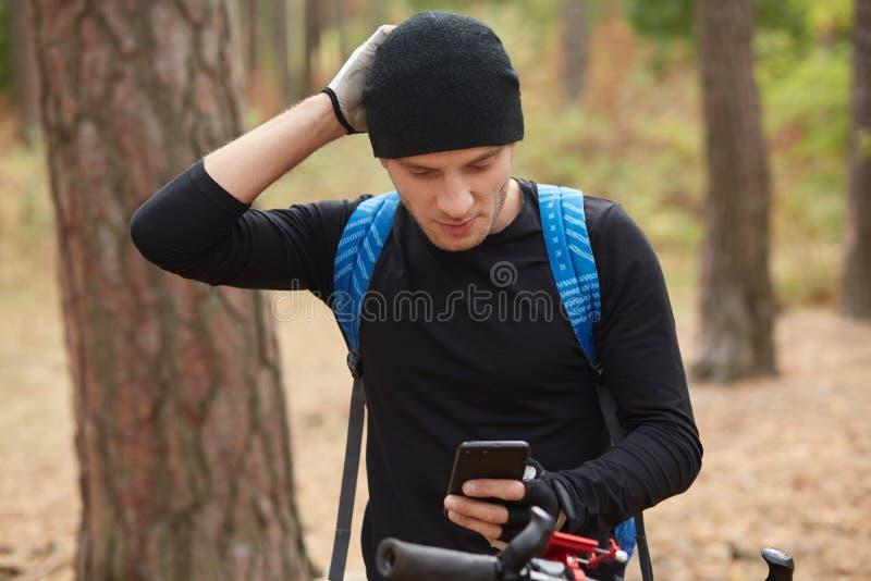 帅气的欧洲年轻自行车手穿着黑色运动装和蓝色背包,迷失在树林里后,用手机给朋友发信息, 免版税图库摄影
