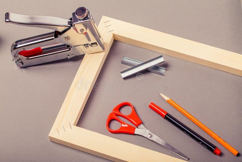帆布、钉书针枪和其他工具的担架在灰色背景 免版税库存照片