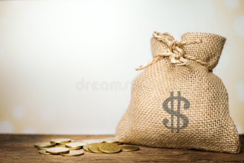帆布在木桌上的金钱大袋 免版税库存照片