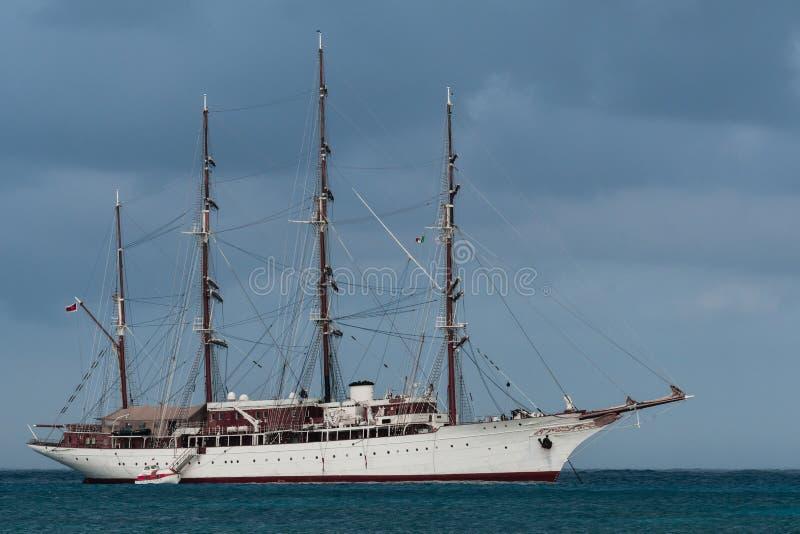 4帆柱高船停住与在科苏梅尔,墨西哥港的一条嫩小船  免版税库存照片