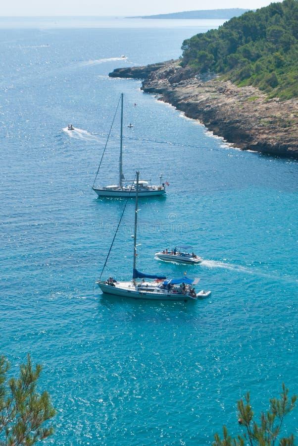 帆船和汽艇在梅诺卡海岛海湾  免版税库存照片
