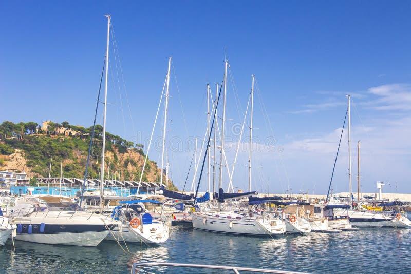 帆船和游艇停放在布拉内斯,布拉瓦海岸,西班牙船坞  有白色游艇的海港在夏天晴天 库存照片