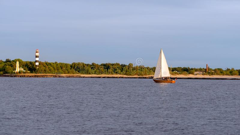 帆船回到沿灯塔的口岸 库存照片