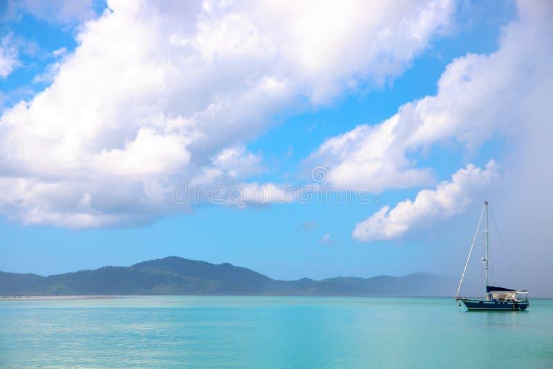帆船在雨云下的土耳其玉色海 美好的热带海岛风景 雨季节天气 免版税图库摄影