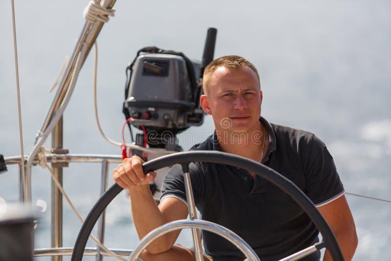 帆船的舵的一位年轻船长 体育运动 免版税库存照片