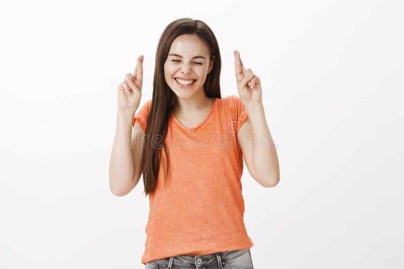 希望咧嘴笑的愉快的女孩赢取在抽奖 橙色T恤杉的迷人的快乐的白种人妇女,举但愿的 库存图片