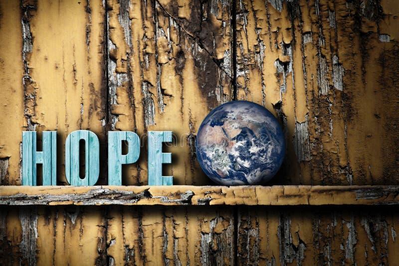 希望文本词和行星地球在破旧的木背景 免版税图库摄影