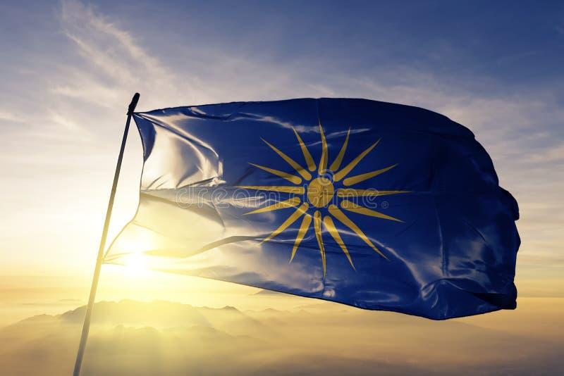 希腊人希腊旗子纺织品挥动在顶面日出薄雾雾的布料织品的马其顿地区 库存例证