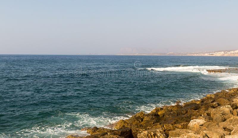 希腊克利特海岛天蓝色的海是残破的在石岸在一个清楚的晴天 免版税库存照片