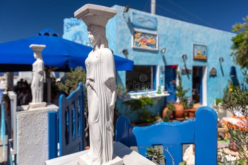 希腊古色古香的雕塑停留在传统村庄入口在Oia镇 免版税图库摄影