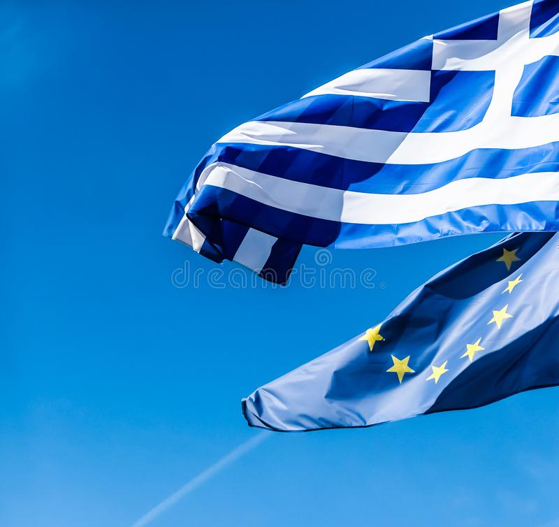 希腊和欧盟旗子在天空蔚蓝背景,欧洲政治  免版税库存图片