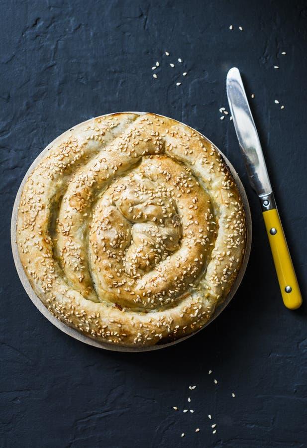希腊在黑暗的背景的菠菜新鲜的乳清干酪油酥点心饼,顶面 Spanakopita饼 免版税库存照片