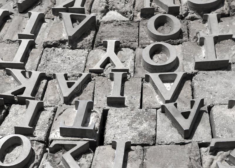 希腊字母表的金属信件在灰色石表面背景的 库存图片