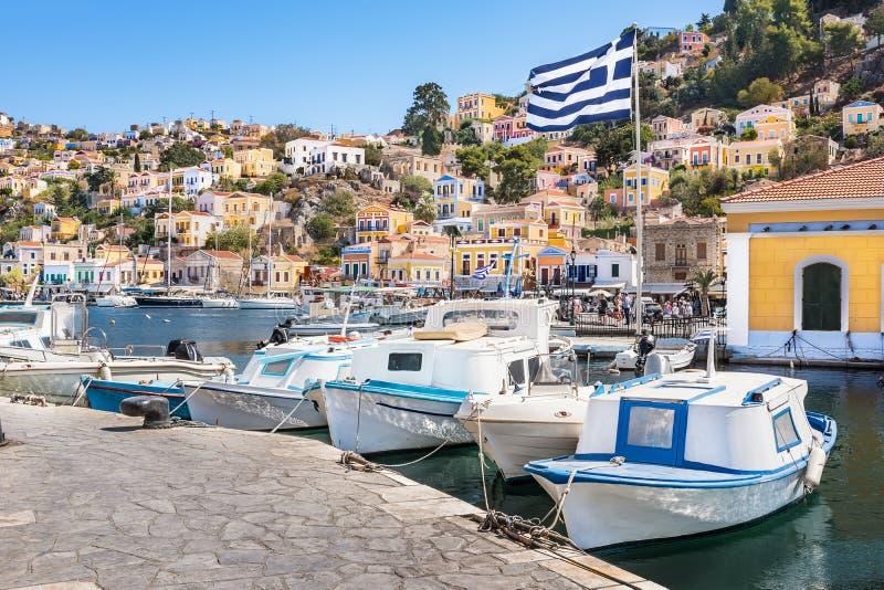 希腊旗子、小船和五颜六色的新古典主义的房子在锡米岛锡米岛海岛,希腊港口镇  图库摄影