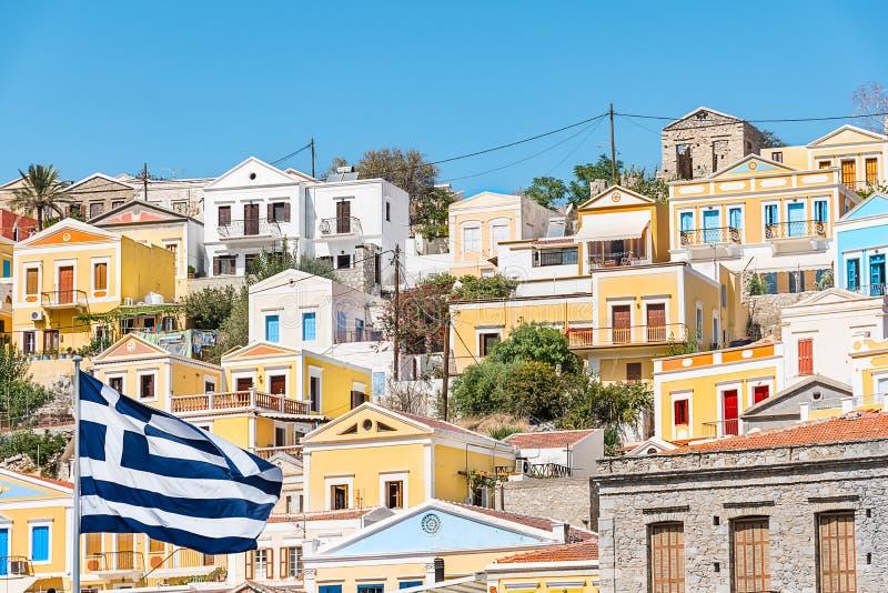 希腊旗子和五颜六色的新古典主义的房子在锡米岛锡米岛海岛,希腊港口镇  免版税库存照片
