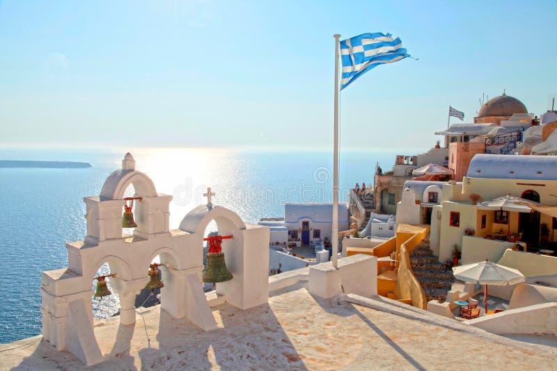 希腊旗子和钟楼在Oia村庄,圣托里尼,希腊 库存图片