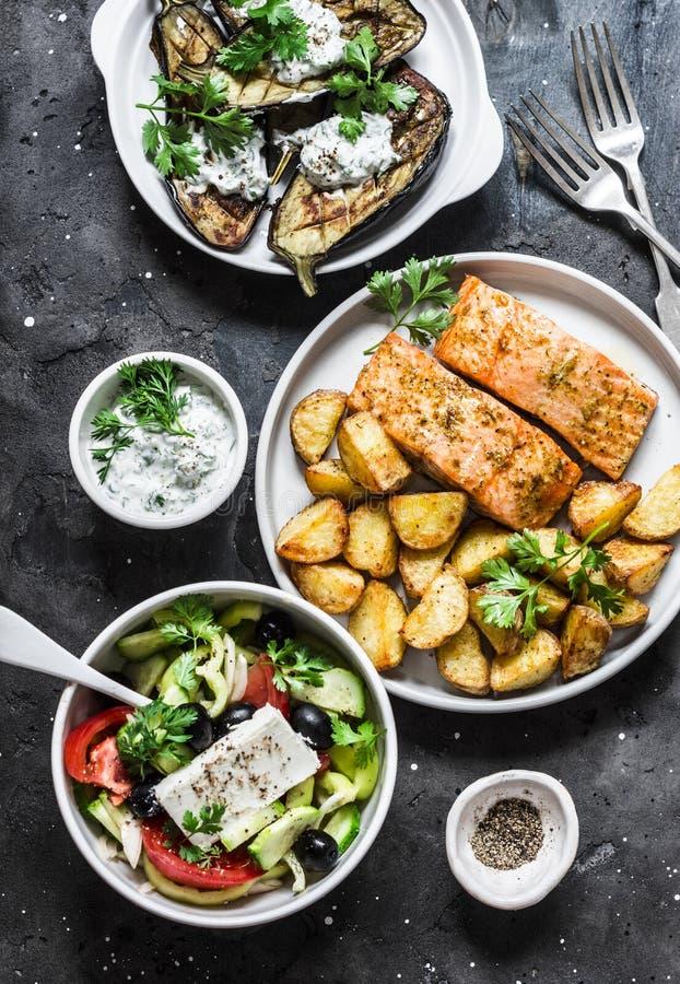希腊样式午餐桌-被烘烤的柠檬三文鱼用土豆,希腊沙拉,烤茄子用在黑暗的背景的tzadziki调味汁, 免版税库存图片