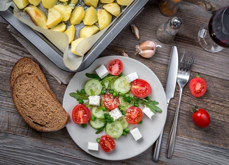 希腊沙拉用乳酪,被烘烤的土豆, topview 图库摄影