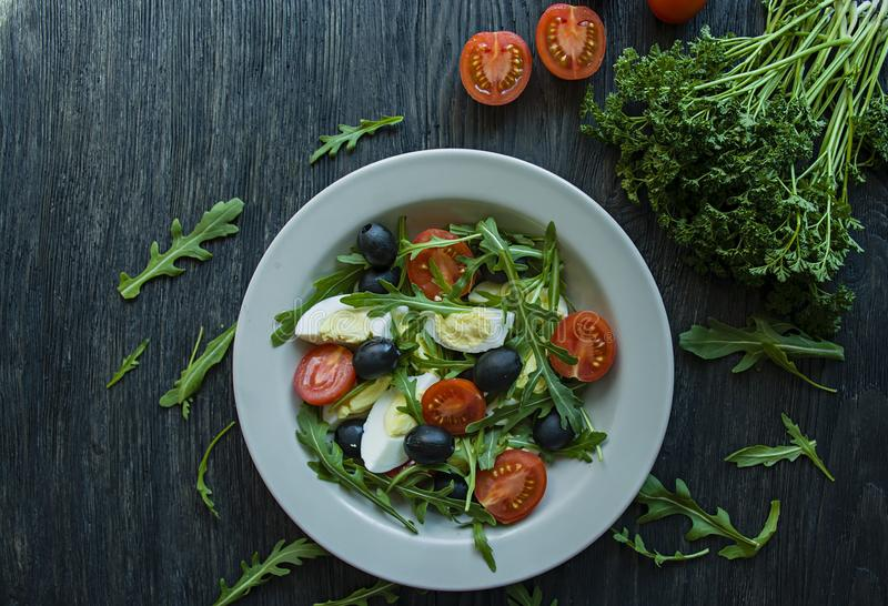 希腊沙拉用新鲜的蕃茄,芝麻菜,鸡蛋,与橄榄油的橄榄在黑暗的木背景 r 素食者盘 库存图片