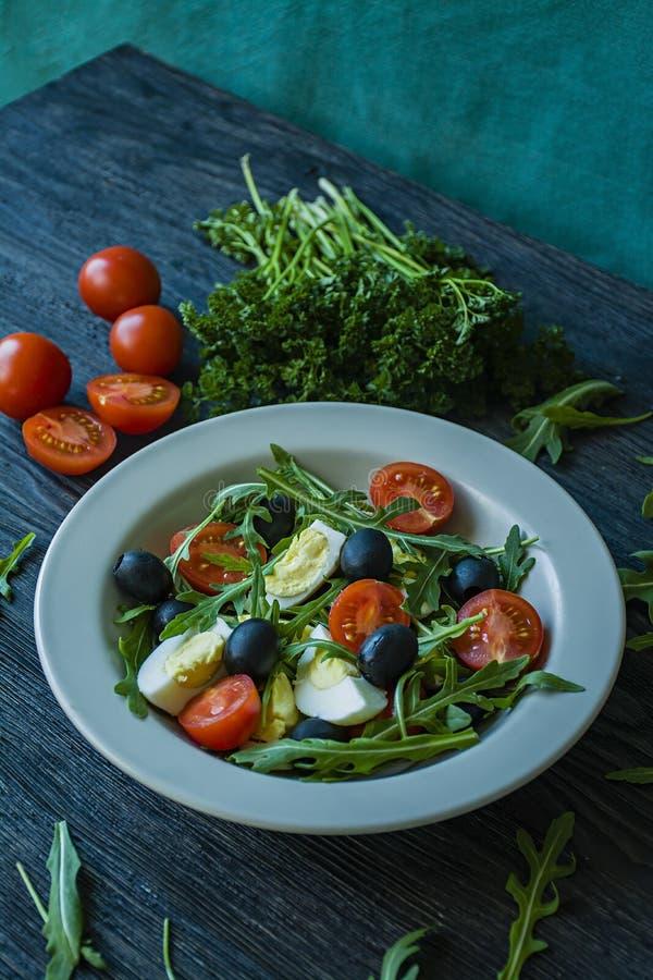 希腊沙拉用新鲜的蕃茄,芝麻菜,鸡蛋,与橄榄油的橄榄在黑暗的木背景 r 素食者盘 图库摄影
