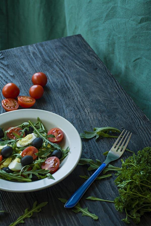 希腊沙拉用新鲜的蕃茄,芝麻菜,鸡蛋,与橄榄油的橄榄在黑暗的木背景 r 素食者盘 库存照片