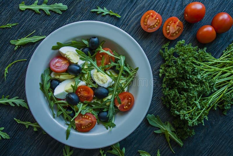 希腊沙拉用新鲜的蕃茄,芝麻菜,鸡蛋,与橄榄油的橄榄在黑暗的木背景 r 素食者盘 免版税库存照片