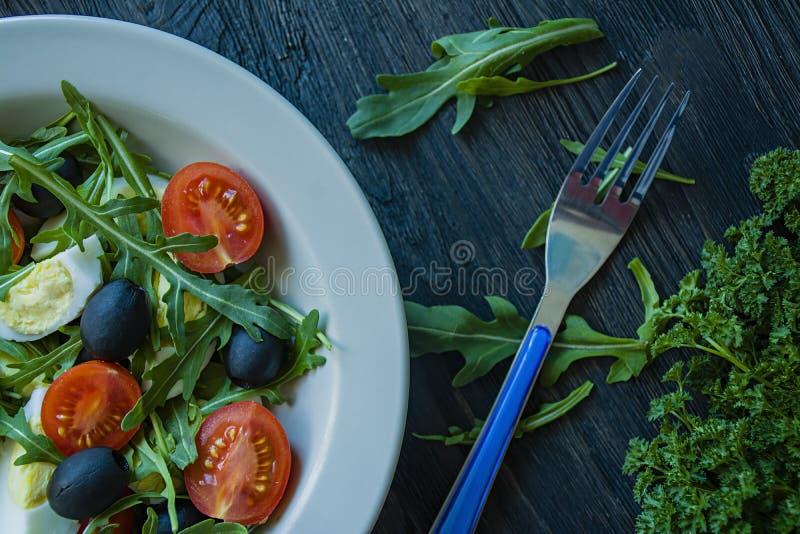 希腊沙拉用新鲜的蕃茄,芝麻菜,鸡蛋,与橄榄油的橄榄在黑暗的木背景 r 素食者盘 免版税图库摄影