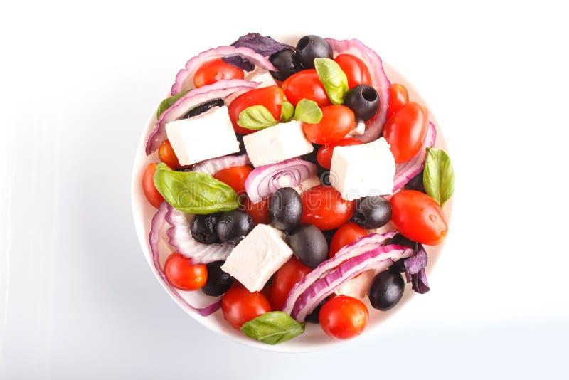 希腊沙拉用新鲜的西红柿、希腊白软干酪、在白色和葱隔绝的黑橄榄、蓬蒿 免版税库存照片