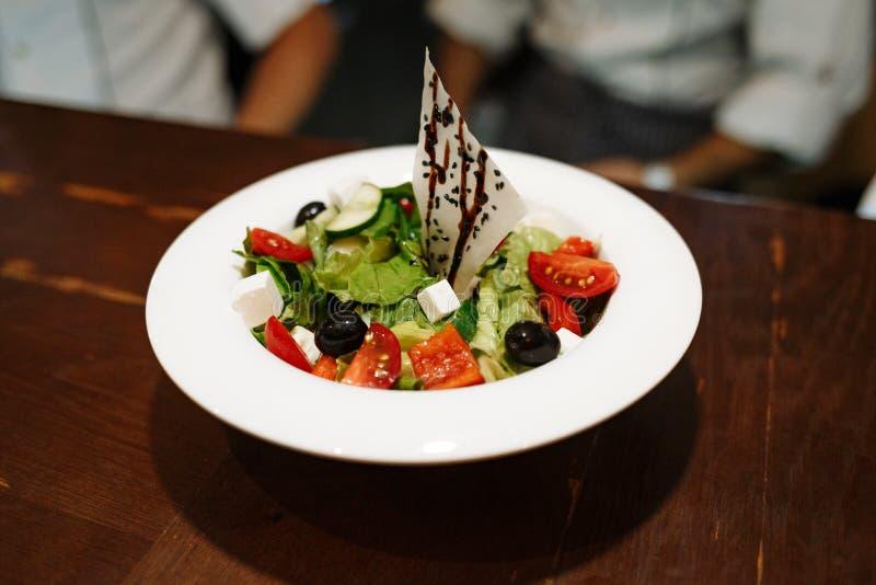 希腊沙拉用橄榄、蕃茄、乳酪和绿色在一块白色板材反对一张木桌 库存图片
