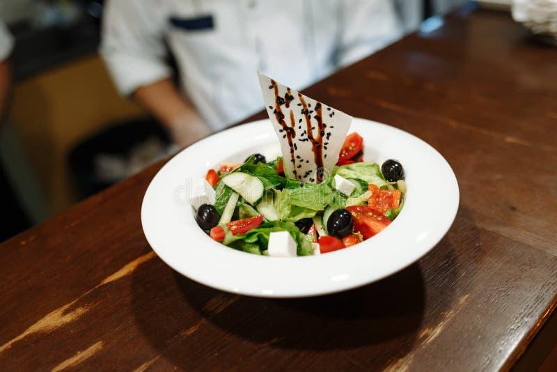 希腊沙拉用橄榄、蕃茄、乳酪和绿色在一块白色板材反对一张木桌 免版税库存图片
