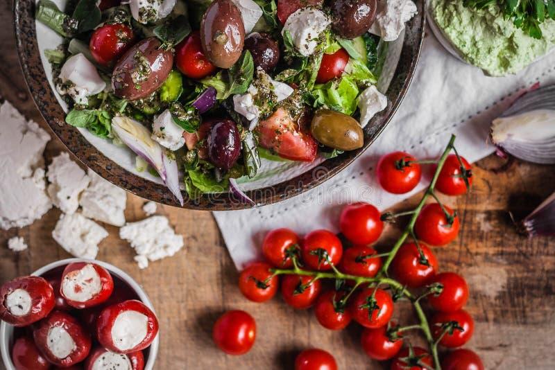 希腊沙拉用西红柿、葱、开胃小菜和希腊白软干酪在木台式视图 免版税库存图片