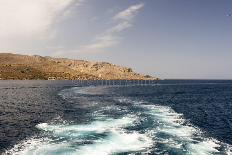 希腊海岛和一艘汽艇的看法在夏时的爱琴海 免版税库存照片