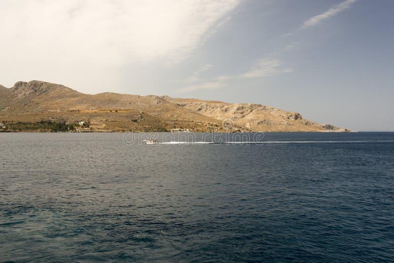 希腊海岛和一艘汽艇的看法在夏时的爱琴海 免版税库存图片