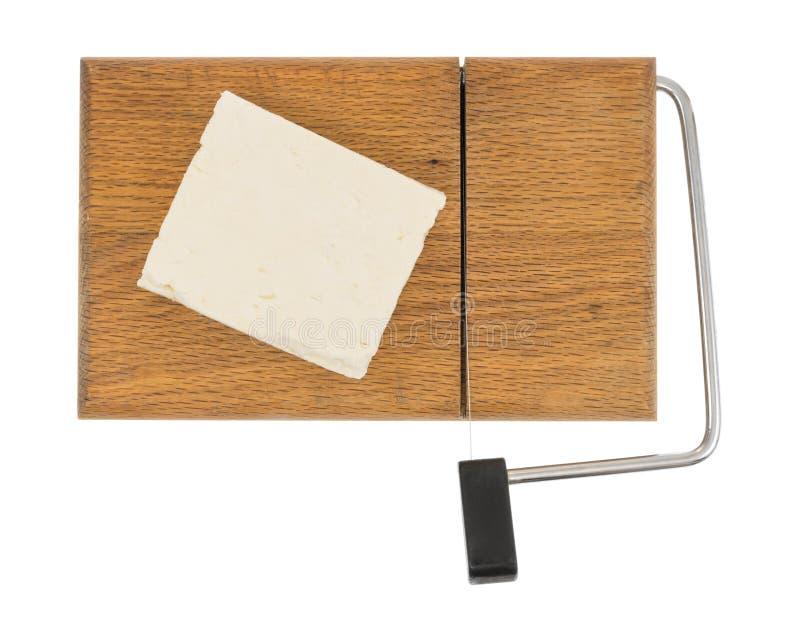 希腊白软干酪块在木乳酪切片机的 免版税库存照片
