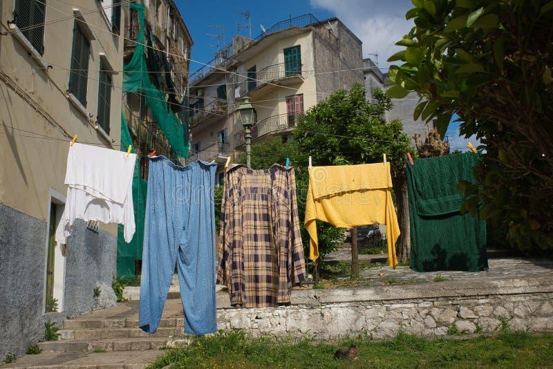 希腊科尔福古老建筑前,一张彩色衣服挂在洗衣绳上 免版税图库摄影