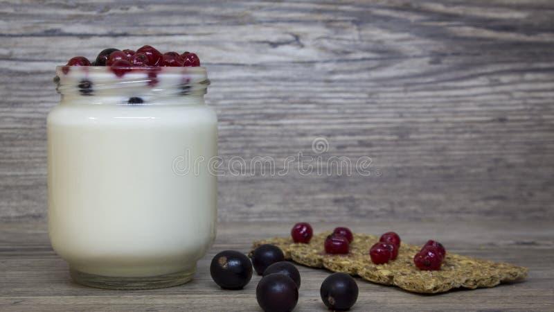希腊酸奶、牛奶、圆滑的人、蓝莓和无核小葡萄干在一个玻璃瓶子在一张木桌,戒毒所,饮食上 免版税库存图片