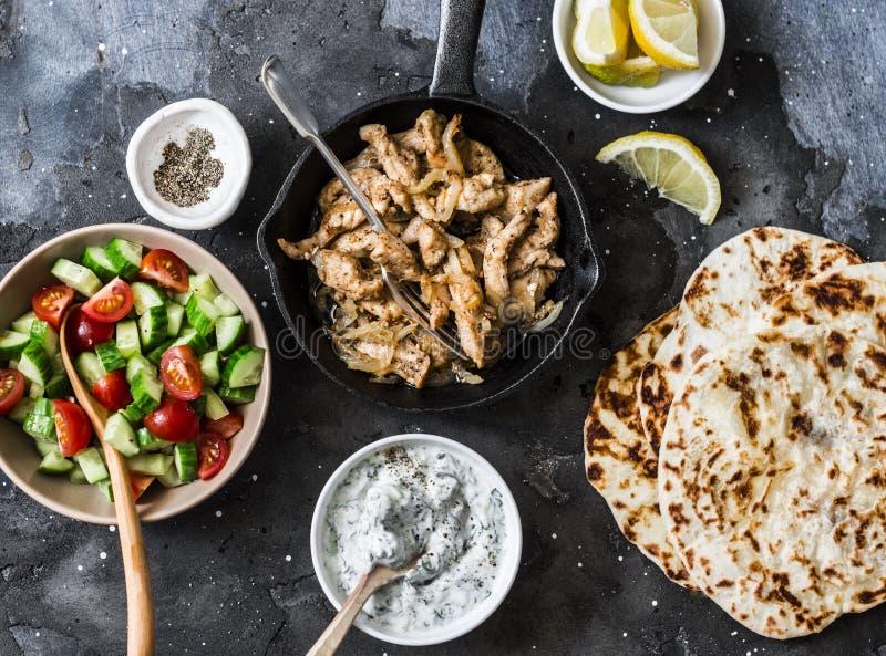 希腊鸡电罗经的-炸鸡、蕃茄黄瓜沙拉、tzatziki调味汁和小面包干成份在黑暗的背景,顶面 免版税图库摄影