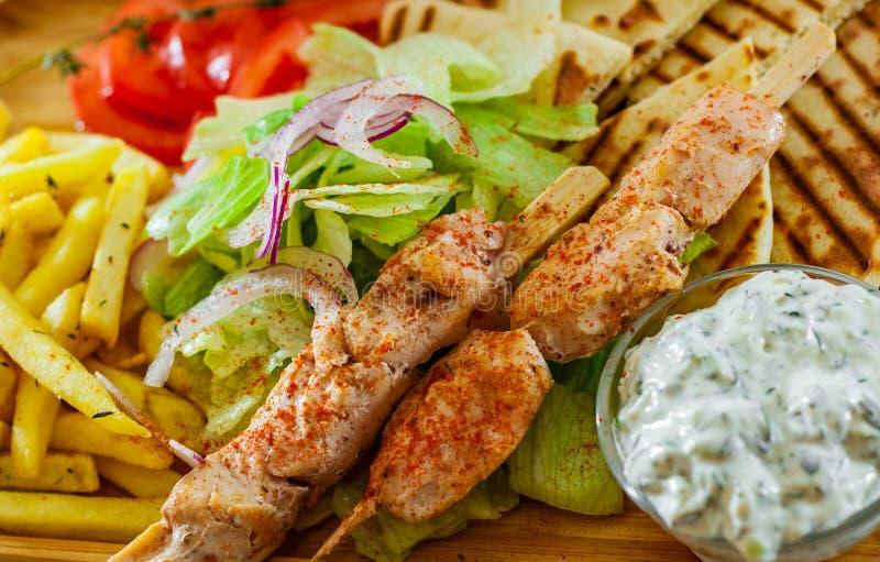 希腊鸡Souvlaki用沙拉、薯条土豆、皮塔饼和tzatziki调味汁 免版税库存图片