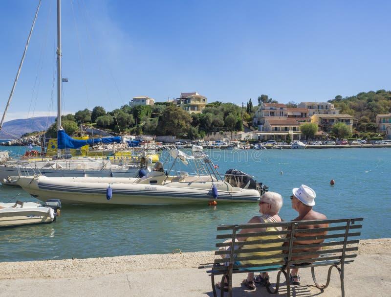 希腊,科孚岛,Kassiopi 2018年9月28日:两对资深人夫妇游人坐在奎伊的长凳有看法  库存图片