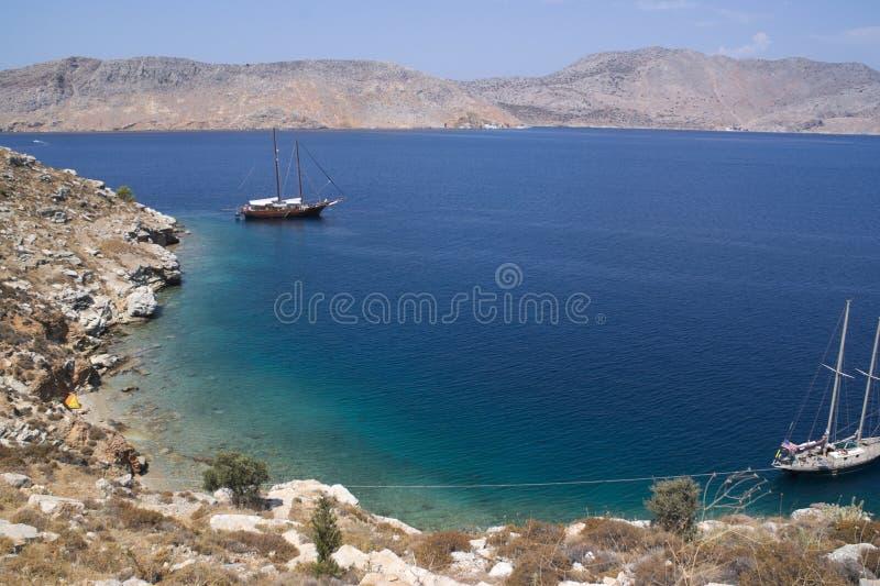 希腊,锡米岛 在海湾的两条风船 免版税库存照片