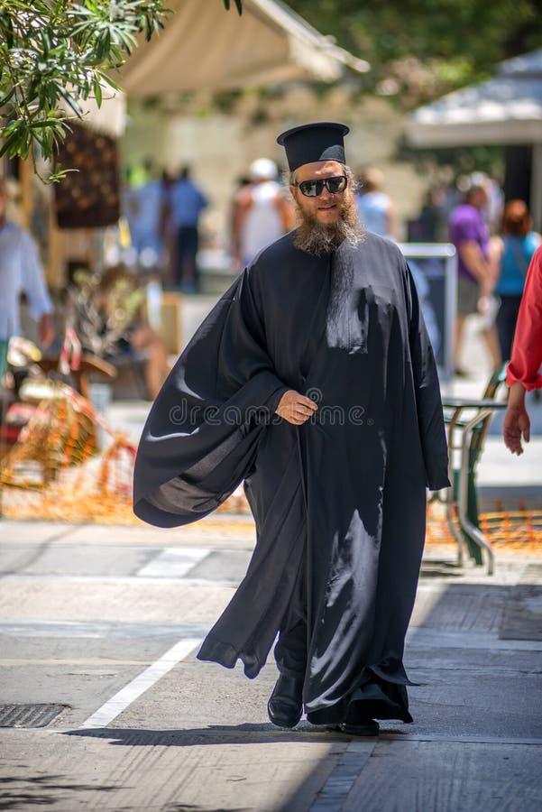 希腊- 7月17 :步行沿着向下街道的一位东正教教士 免版税库存照片