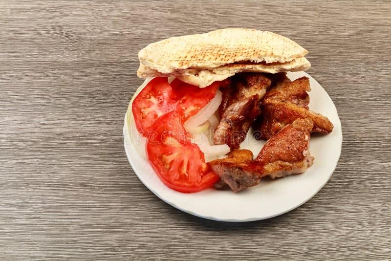 希腊souvlaki用皮塔饼面包和菜特写镜头在桌上 猪肉桌 免版税库存照片