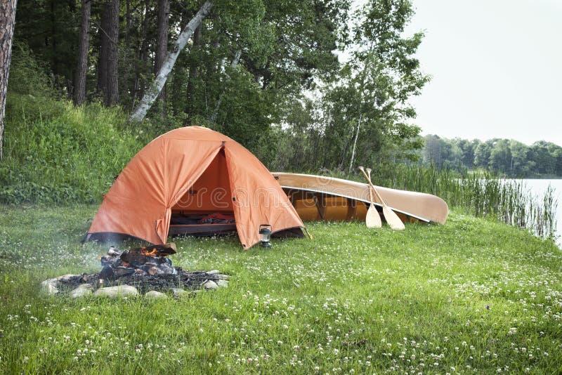 帐篷、营火和独木舟在明尼苏达lakshore 库存图片