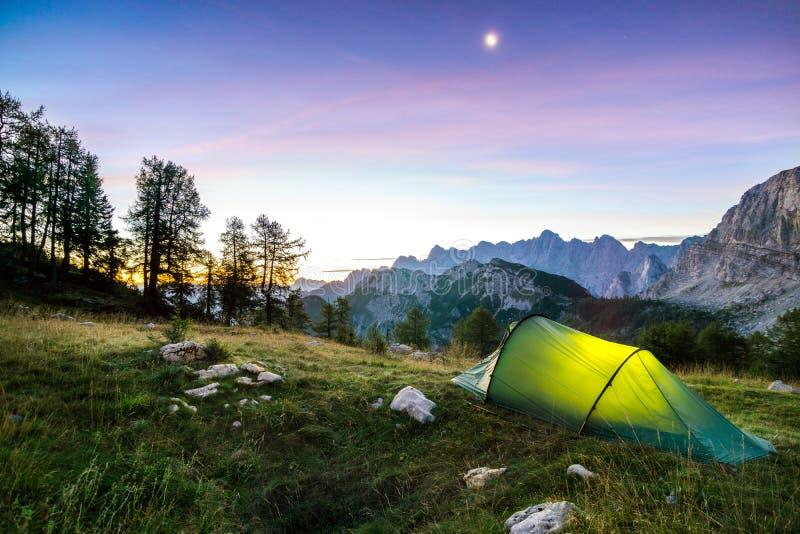 帐篷发光在月亮夜空下在暮色小时 阿尔卑斯,特里格拉夫峰国家公园,斯洛文尼亚 免版税库存照片