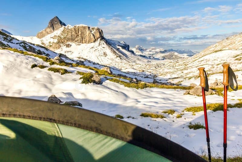 帐篷和远足棍子在多雪的山环境美化 迁徙在瑞士阿尔卑斯 Hoch Turm, Charetalp,瑞士 免版税库存图片