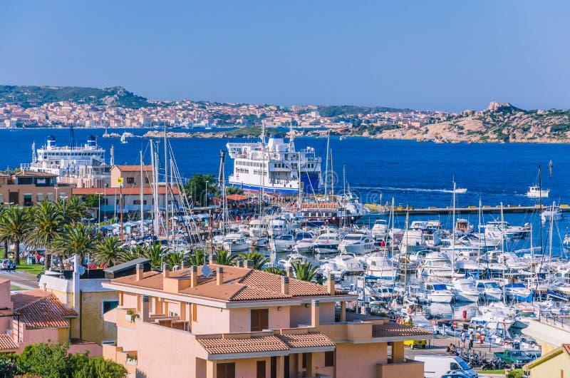 帕劳的港在撒丁岛海岛上的有farry和游艇小船的 拉马达莱纳海岛在背景中 免版税图库摄影