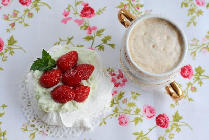帕夫洛娃蛋糕用与一个杯子的草莓在一块五颜六色的餐巾的热奶咖啡 免版税图库摄影