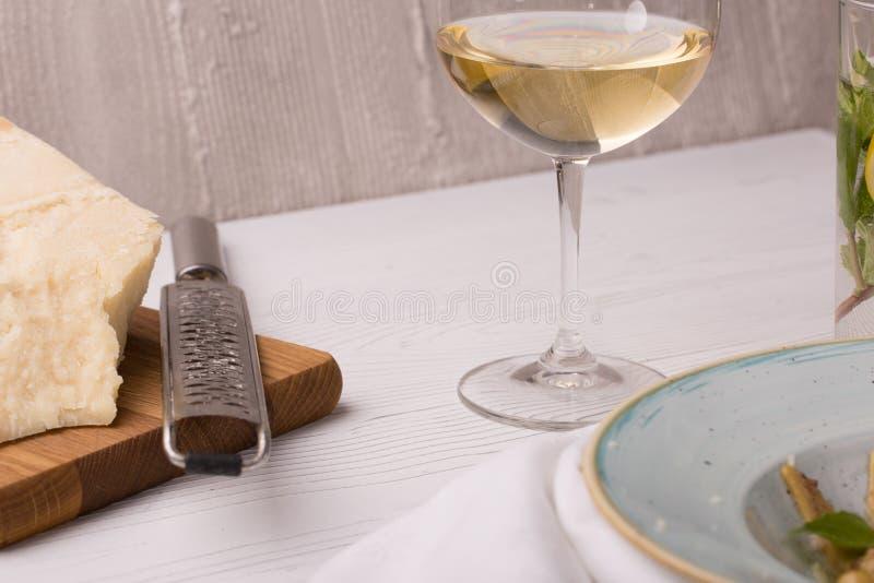 帕尔马干酪片断与磨丝器和白葡萄酒的在切板 免版税库存照片